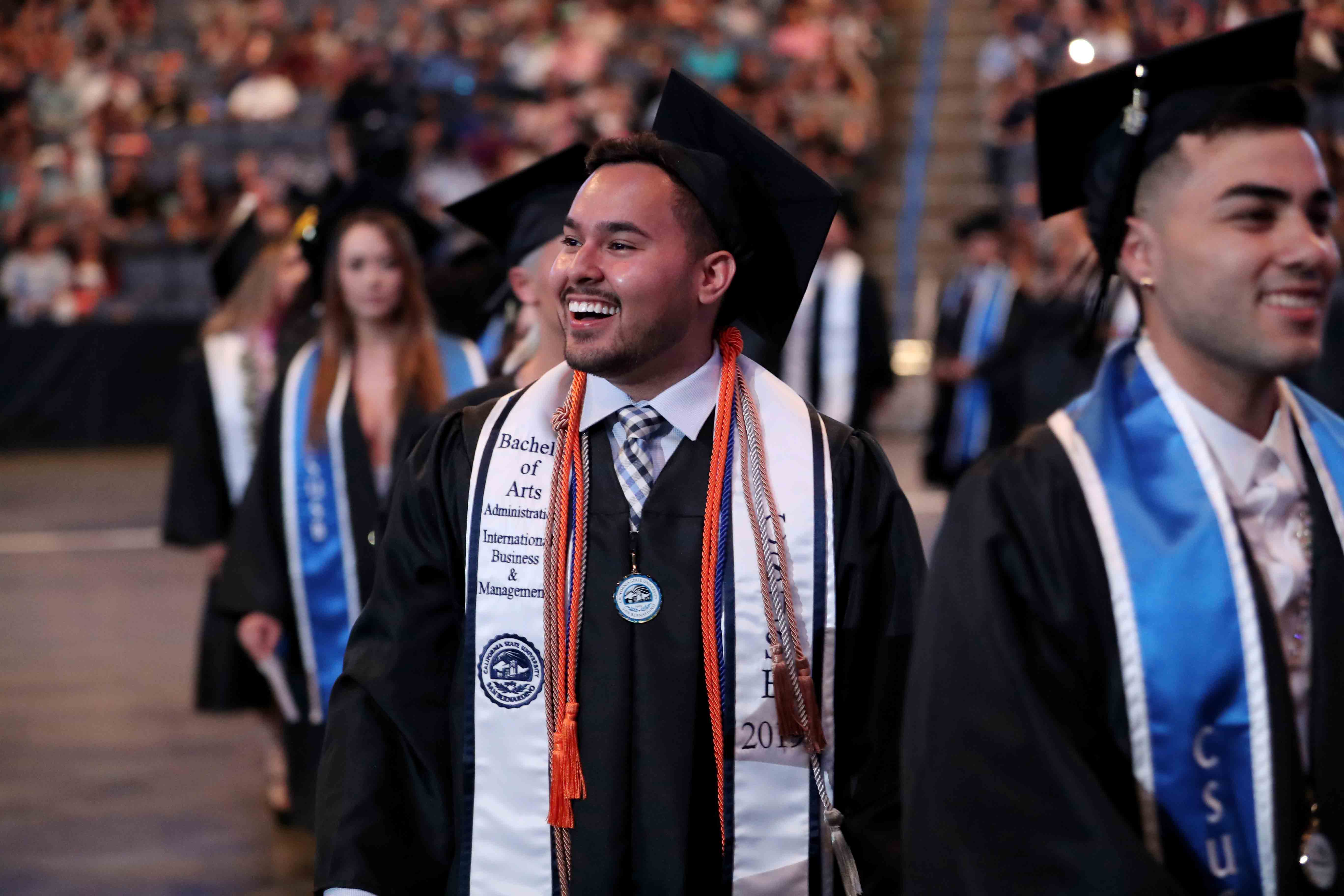 A student marches into Toyota Arena for one of four commencement ceremonies.