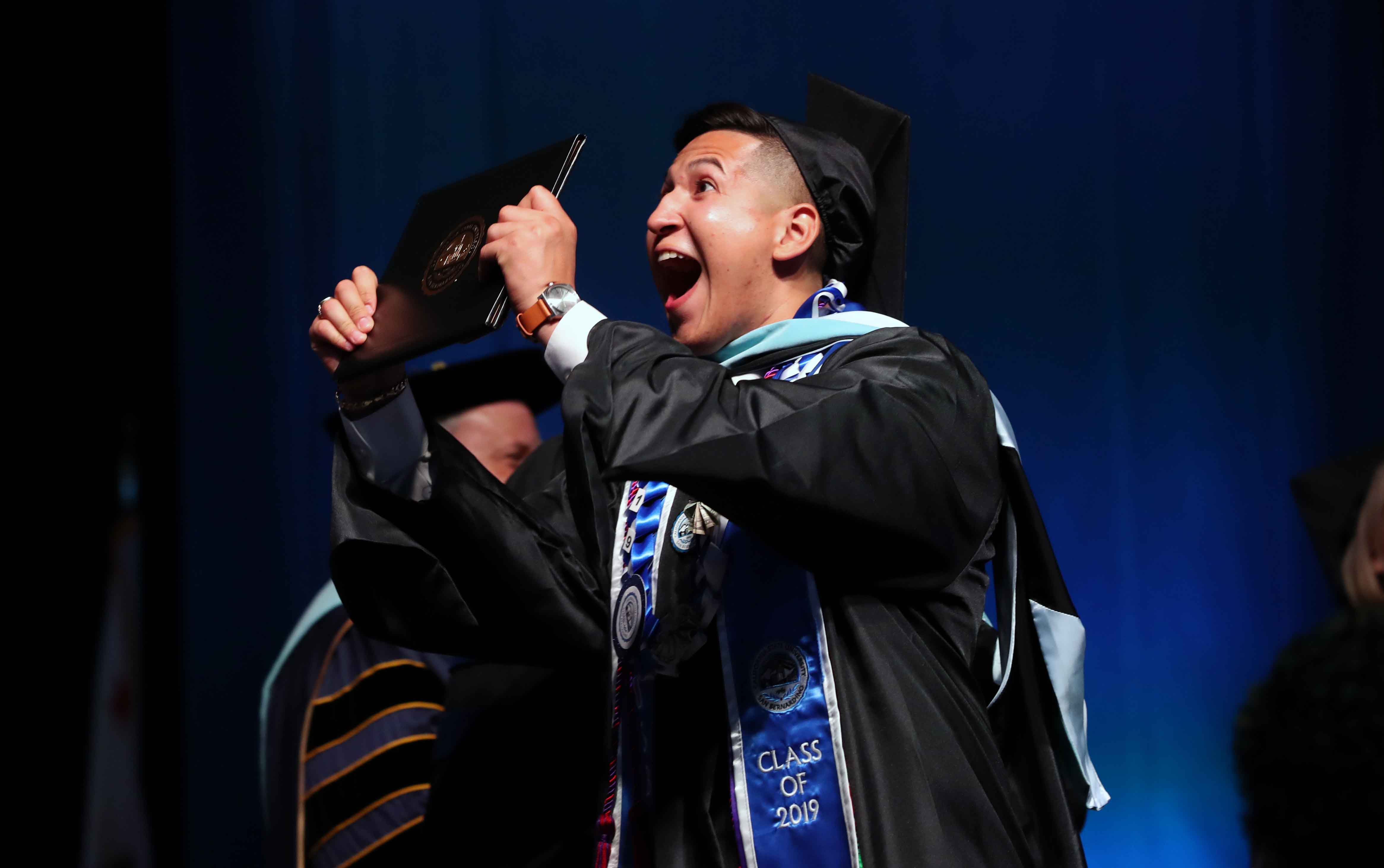 A student celebrates at one of four CSUSB commencement ceremonies at Toyota Arena