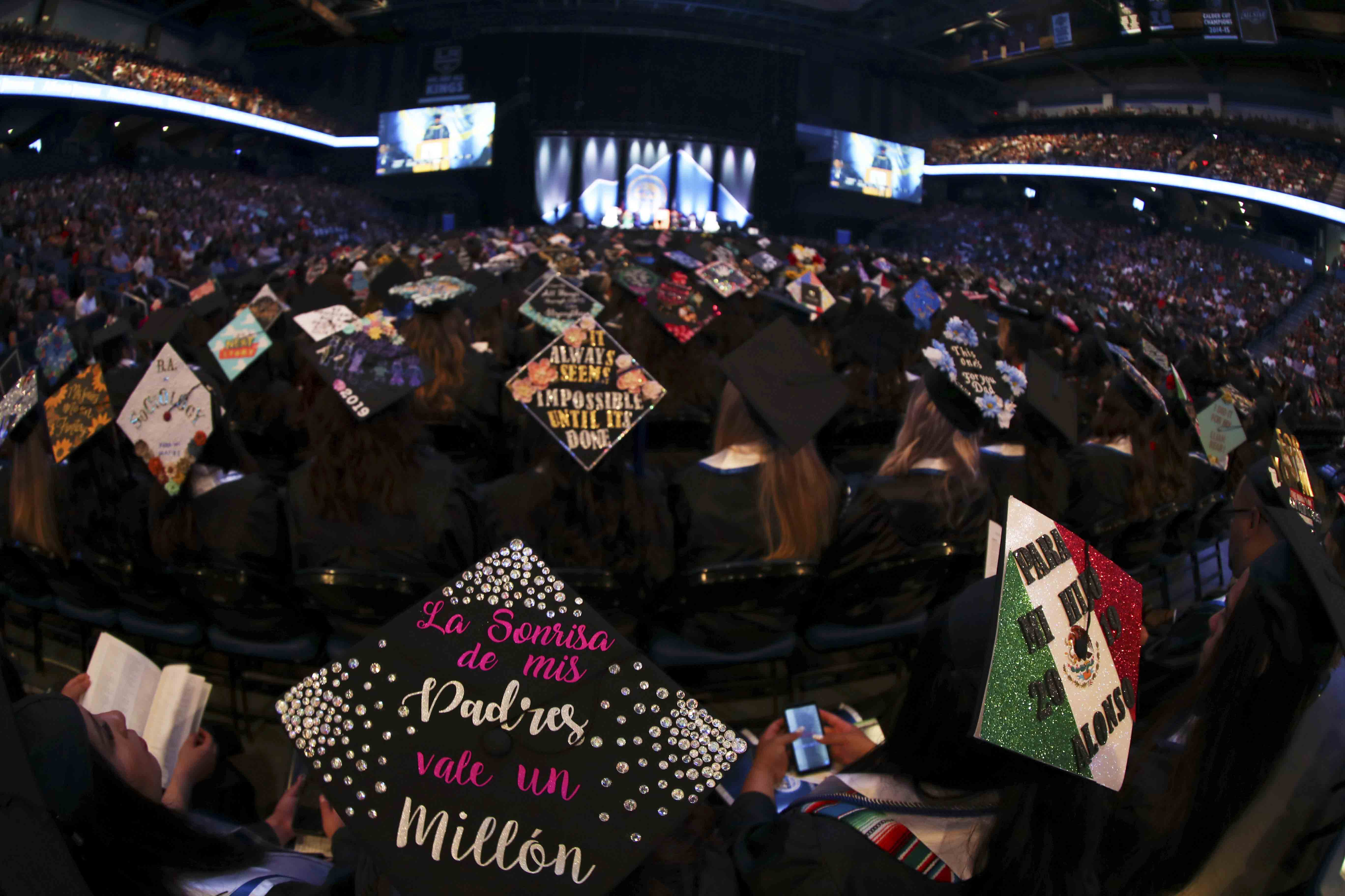 Decorated mortar boards at a CSUSB commencement ceremony at Toyota Arena